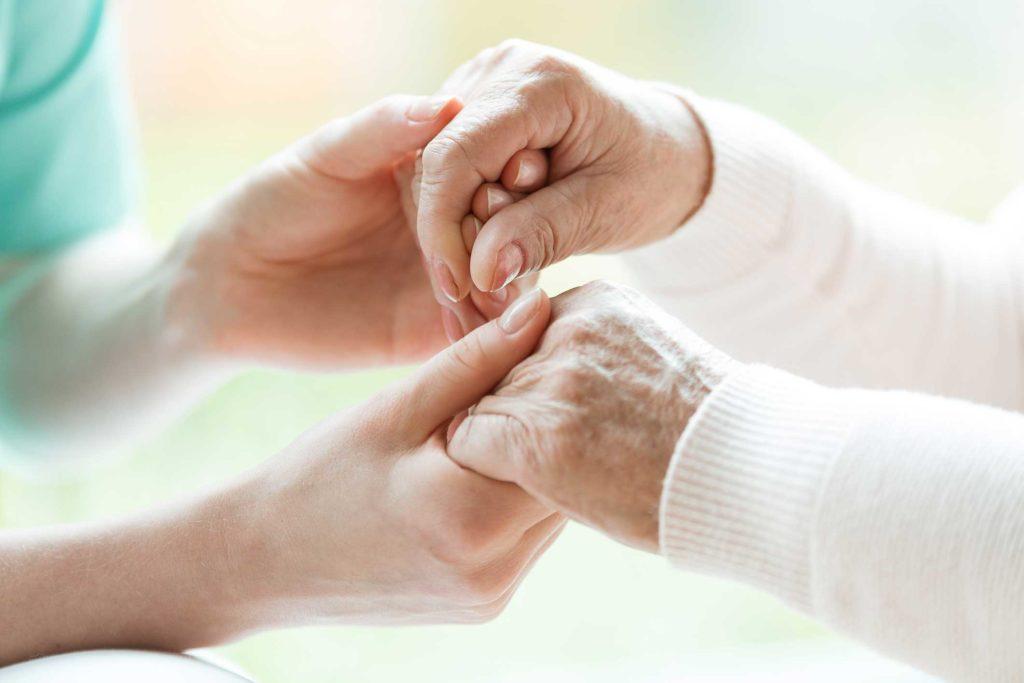Geförderte Palliativstudie - Zwei Personen halten sich an den Händen